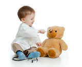 Adorable boy with clothes of doctor is spoon-feeding teddy bear