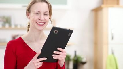 lächelnde frau mit tablet-computer in der küche