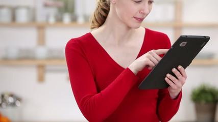 junge frau benutzt ihren tablet-computer in der küche