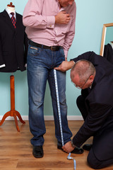 Man having inside leg measured by a tailor for a bespoke suit