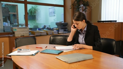 Attractive woman talking on the phone in office