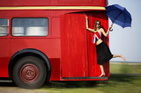 Young woman going by red bus