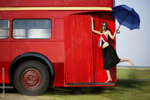 In de dag Londen rode bus Young woman going by red bus