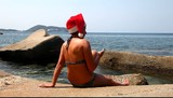 Woman on the beach in santa hat calls on the phone