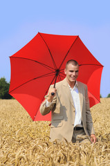 Young agronomist with red sun umbrella in the wheat