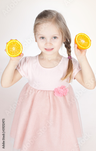 Beautiful little blonde girl holding fresh oranges