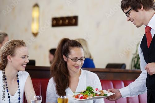 freundlicher kellner serviert einen salat