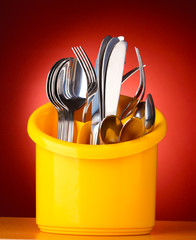 Kitchen cutlery, knives, forks and spoons in yellow stand