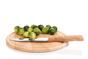 Brussels sprouts on wooden chopping board isolated on white