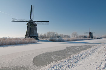 two windmills on frozen canal