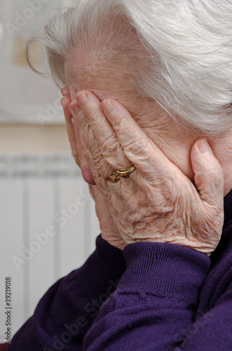 A crying elderly woman covering her fac