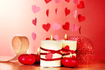 candles for Valentine's Day on wooden table on red background