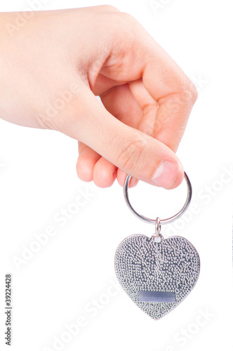 Female hand holding metal fob in the shape of heart