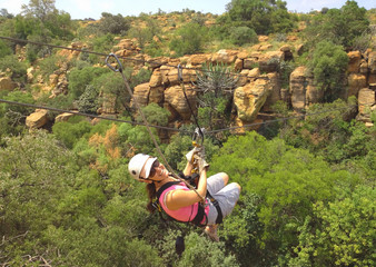 Lady sliding on a zip line across a gorge