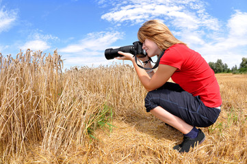 girl taking photos in wheat field