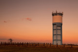 Historic water reservoir brick tower at sunset poster