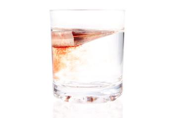 Пакетик чая заваривается в стакане с водой на белом фоне