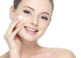 Beautiful smiling woman applying  cream on cheek