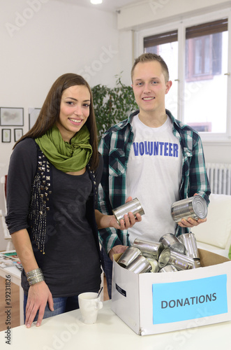 young volunteer couple with food donation box