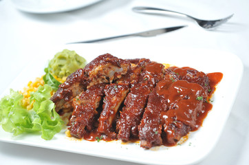 Closeup of barbecued pork ribs and vegetables