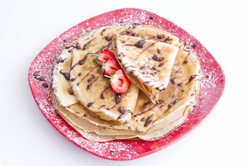 sweet pancakes with strawberries on red plate