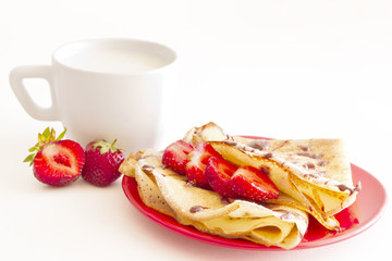 cup of milk and sweet pancakes with strawberry