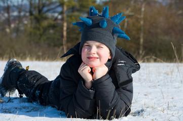 boy is lying in the snow- meadow