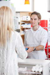 Male Pharmacist With A Customer In Pharmacy