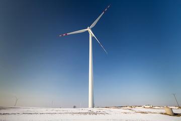 Wind turbine over blue sky on winter field
