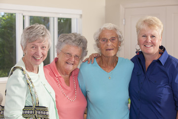 Portrait of four senior female friends smiling together
