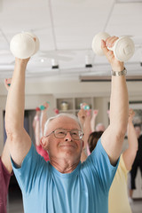 Senior exercise class doing arm stretches