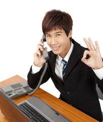 Young businessman  holding phone with OK hand gesture