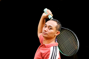 handsome ethnic young man with tennis racket on hand