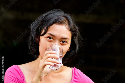 thirsty ethnic young woman drinking pure mineral water