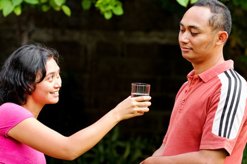 ethnic young woman offer pure mineral water to male friend
