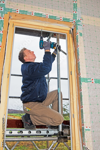 carpenter mounting a new window