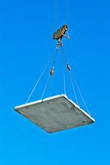 Construction - crane lifting a concrete plate in blue sky