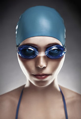 Stylish portrait of a young woman in goggles and swimming cap