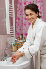 Young woman washing hands in bathroom