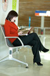Beautiful female tourist in the airport with laptop, waiting for