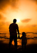 the silhouette of father holding little girl's hand on the beach