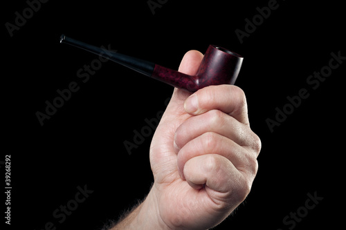 smoking pipe in hand isolated on black background