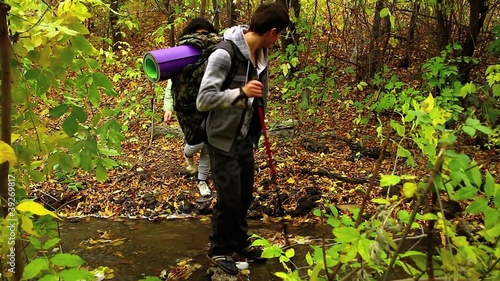 Young hiking couple crossing a stream in autumn forest