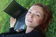 Redhead woman laying on the grass, holding a laptop
