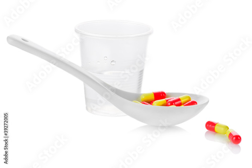 Pharmacy. Antibiotic pills in spoon and plastic glass of water