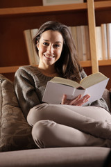 Portrait of a happy young woman lying on couch with book