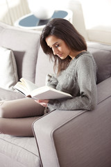 Portrait of a  young woman lying on couch with book