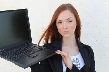 Pretty redhead woman holding a laptop