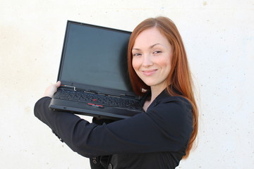 Pretty redhead woman holding a laptop