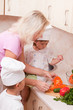 Mum with children prepares for vegetable salad on kitchen